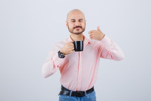 Jonge man in roze shirt, spijkerbroek die de geur van thee voelt, vooraanzicht.