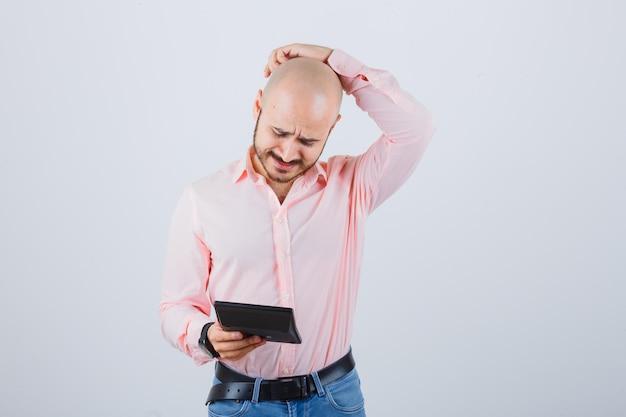 Jonge man in roze shirt, spijkerbroek die naar rekenmachine kijkt terwijl hij aan zijn hoofd krabt, vooraanzicht.