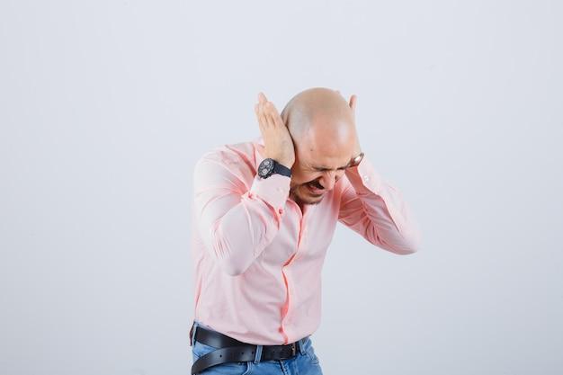 Jonge man in roze shirt, spijkerbroek hand in hand op oren terwijl hij naar voren buigt en er gek uitziet, vooraanzicht.