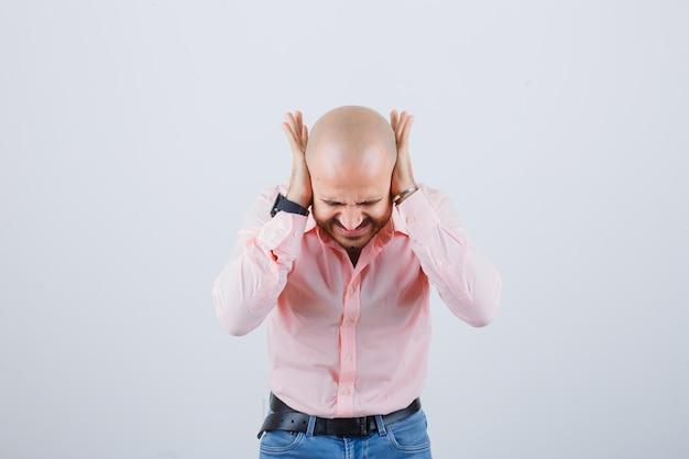 Jonge man in roze shirt, spijkerbroek hand in hand op oren terwijl hij naar voren buigt en er stressvol uitziet, vooraanzicht.