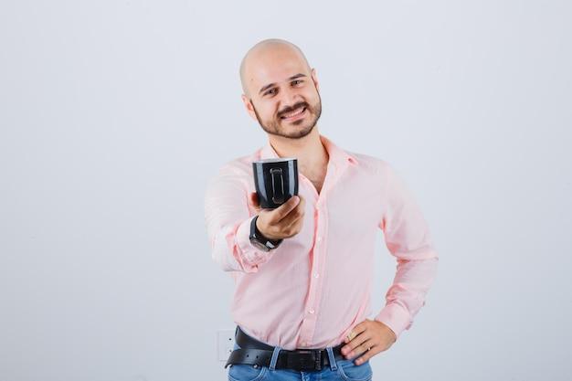 Jonge man in roze shirt, spijkerbroek met beker terwijl hij lacht, vooraanzicht.