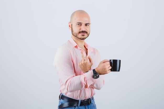 Jonge man in roze shirt, spijkerbroek met beker terwijl hij middelvinger laat zien, vooraanzicht.