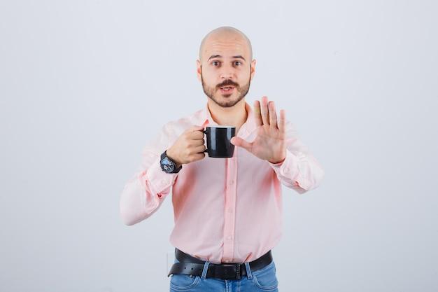 Jonge man in roze shirt, spijkerbroek met beker terwijl hij stopgebaar toont en gealarmeerd kijkt, vooraanzicht.