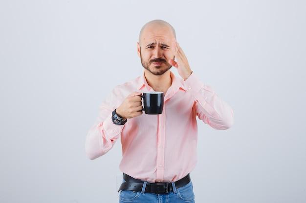 Jonge man in roze shirt, spijkerbroek met beker tijdens het spreken, vooraanzicht.
