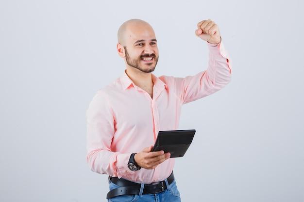 Jonge man in roze shirt, spijkerbroek met rekenmachine terwijl hij succesgebaar toont en er vrolijk uitziet, vooraanzicht.