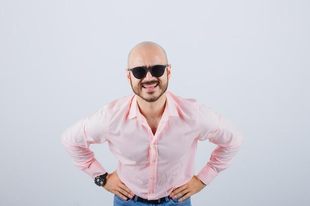 Jonge man in roze shirt, spijkerbroek, zonnebril die iets vraagt met de handen op de taille en er nieuwsgierig uitziet, vooraanzicht.