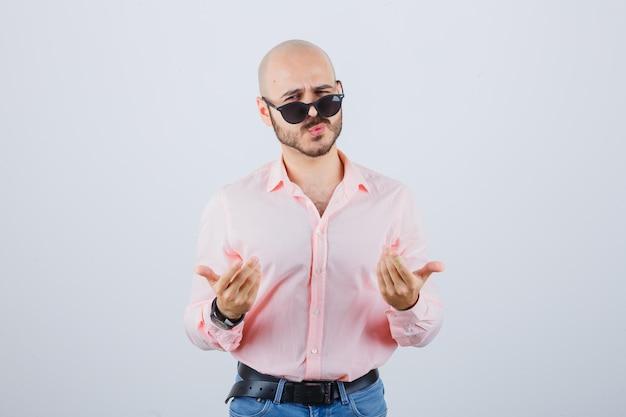 Jonge man in roze shirt, spijkerbroek, zonnebril die zijn gevoelens uitdrukt met handgebaren en er raar uitziet, vooraanzicht.