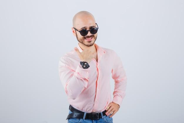Jonge man in roze shirt, spijkerbroek, zonnebril met duim omhoog en zelfverzekerd, vooraanzicht.