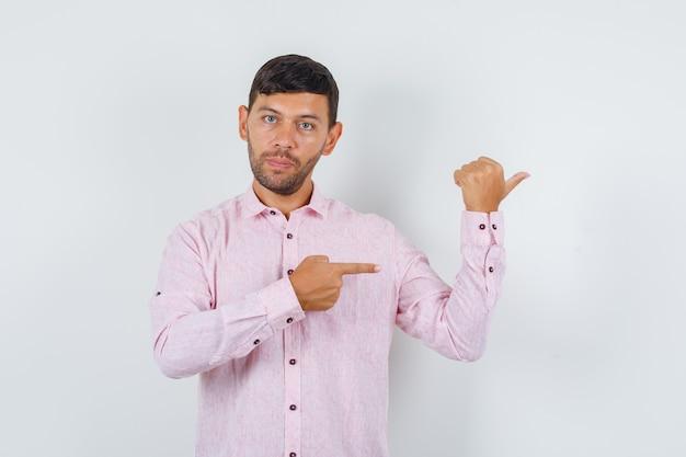 Jonge man in roze shirt wijst naar kant, vooraanzicht.