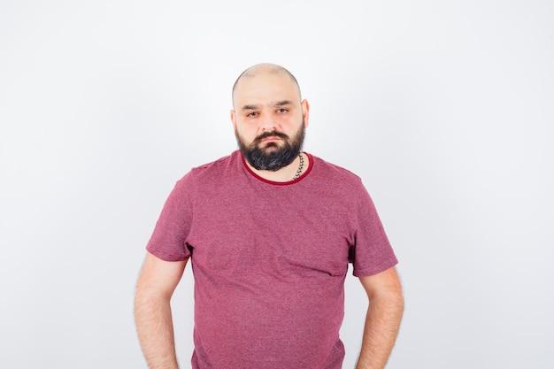 Jonge man in roze t-shirt camera kijken en ongevoelig kijken, vooraanzicht.