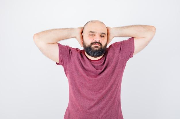 Jonge man in roze t-shirt die de handen op de oren drukt en er serieus uitziet, vooraanzicht.