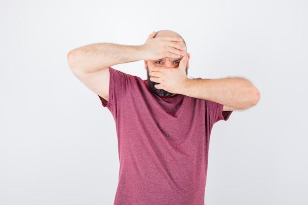 Jonge man in roze t-shirt die door handen kijkt en er serieus uitziet, vooraanzicht.