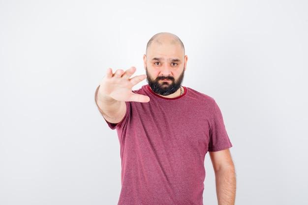 Jonge man in roze t-shirt die hand naar camera uitstrekt als uitnodigend om te komen en er serieus uit te zien, vooraanzicht.