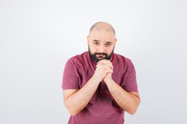 Jonge man in roze t-shirt die handen in gebedspositie omklemt en er gefocust uitziet, vooraanzicht.