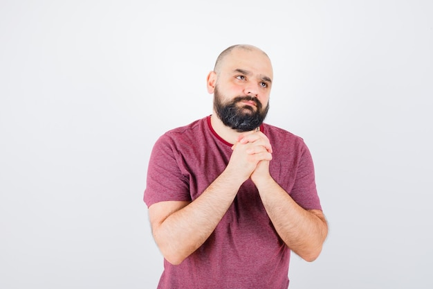 Jonge man in roze t-shirt die handen in gebedspositie omklemt en peinzend kijkt, vooraanzicht.