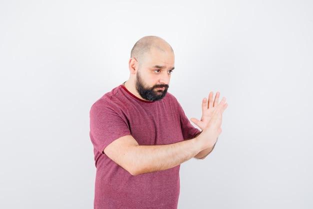 Jonge man in roze t-shirt die handen opsteekt om te verdedigen en er voorzichtig uit te zien, vooraanzicht.