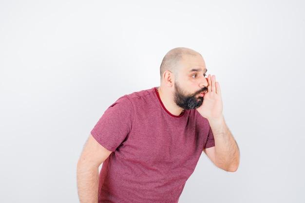 Jonge man in roze t-shirt die in het geheim praat en er geconcentreerd uitziet, vooraanzicht.