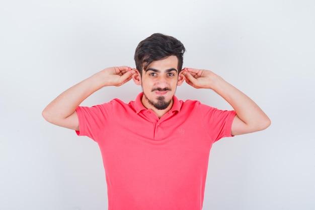 Jonge man in roze t-shirt die oren naar beneden trekt en er schattig uitziet, vooraanzicht.