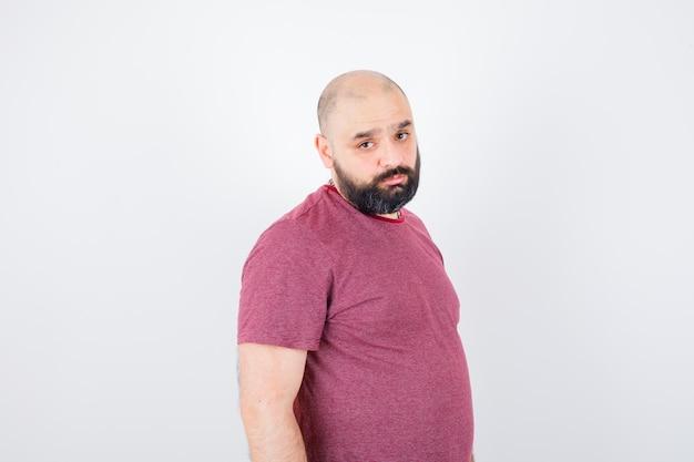 Jonge man in roze t-shirt die rechtop staat, over de schouder kijkt en voor de camera poseert en er serieus uitziet, vooraanzicht.