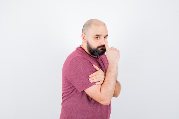 Jonge man in roze t-shirt die stiltegebaar toont en er koud uitziet.