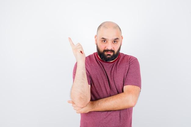 Jonge man in roze t-shirt die wijsvinger opheft in eureka-gebaar en er verstandig uitziet, vooraanzicht.