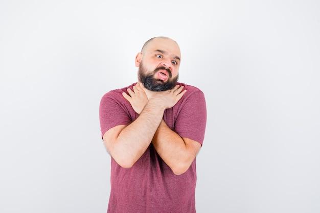 Jonge man in roze t-shirt die zichzelf wurgt, vooraanzicht.
