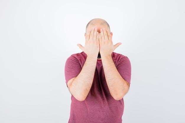 Jonge man in roze t-shirt die zijn gezicht bedekt met handen en er serieus uitziet, vooraanzicht.