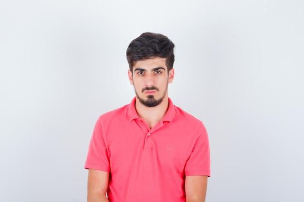 Jonge man in roze t-shirt en ziet er verstandig uit. vooraanzicht.