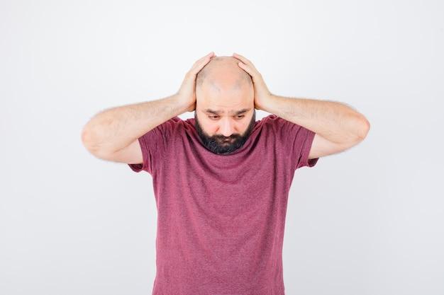 Jonge man in roze t-shirt hand in hand op het hoofd terwijl hij naar beneden kijkt en er treurig uitziet, vooraanzicht.