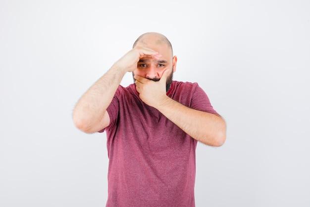 Jonge man in roze t-shirt hand op mond terwijl hij wegkijkt en doodsbang kijkt, vooraanzicht.