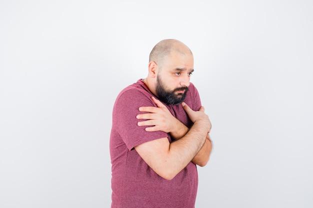 Jonge man in roze t-shirt knuffelt zichzelf en ziet er koud uit.