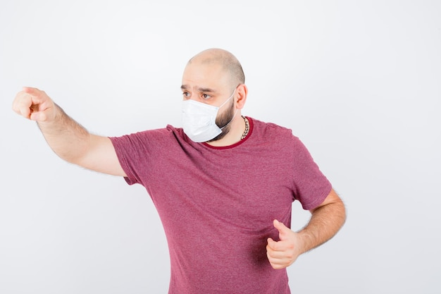 Jonge man in roze t-shirt, masker dat naar voren wijst en er gefocust uitziet, vooraanzicht.