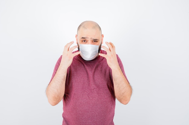 Jonge man in roze t-shirt, masker die handen op een agressieve manier opheft en er nerveus uitziet, vooraanzicht.