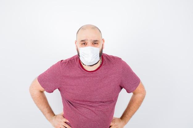 Jonge man in roze t-shirt, masker hand in hand op taille en gefocust, vooraanzicht.
