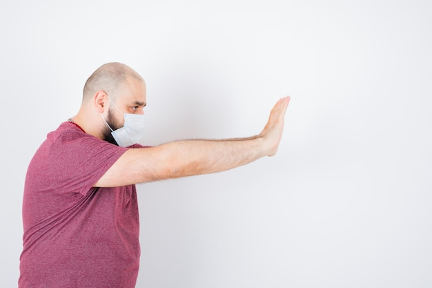 Jonge man in roze t-shirt, masker met stopgebaar.