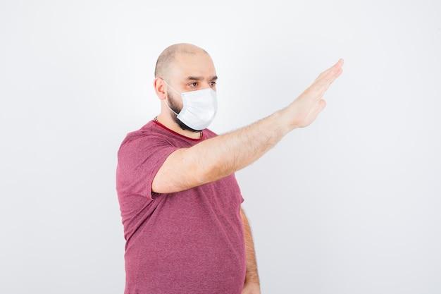 Jonge man in roze t-shirt, masker zwaaiende hand voor afscheid, vooraanzicht.