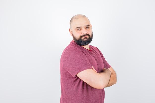 Jonge man in roze t-shirt staande armen gekruist, over de schouder kijkend en serieus kijkend, vooraanzicht.