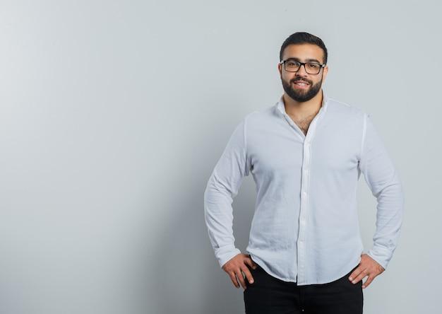 Jonge man in shirt, broek hand in hand op taille en op zoek zelfverzekerd