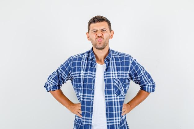 Jonge man in shirt fronsend terwijl hand in hand op de taille en somber, vooraanzicht op zoek.