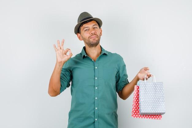 Jonge man in shirt, hoed met papieren zakken met ok teken en op zoek vrolijk