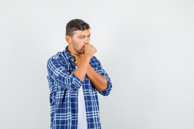 Jonge man in shirt hoest lijden en ziek, vooraanzicht kijken.