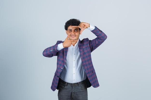 Jonge man in shirt, jas, broek die framegebaar maakt en er zelfverzekerd uitziet, vooraanzicht.