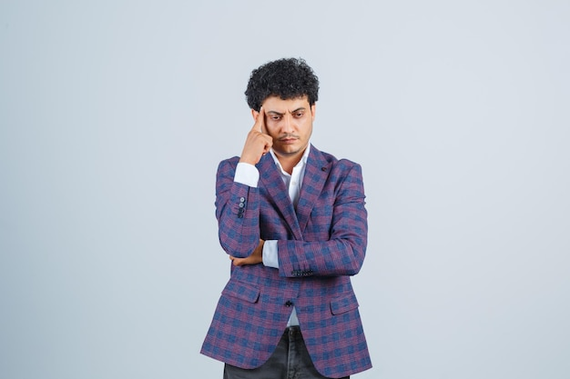 Jonge man in shirt, jas, broek die in denkende pose staat en er verstandig uitziet, vooraanzicht.