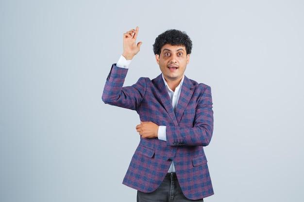 Jonge man in shirt, jas, broek die omhoog wijst door de hand op te steken en er gelukkig uit te zien, vooraanzicht.