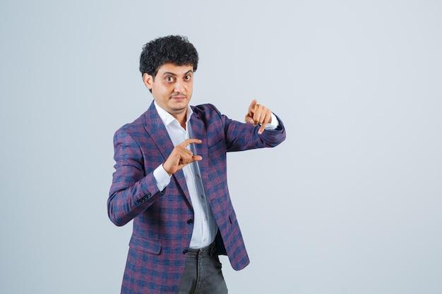 Jonge man in shirt, jas, broek met een klein bordje, wijzend op de camera en zelfverzekerd, vooraanzicht.