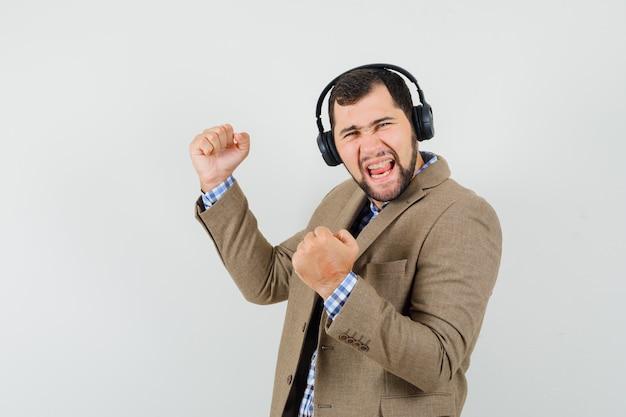 Jonge man in shirt, jasje genieten van muziek met een koptelefoon