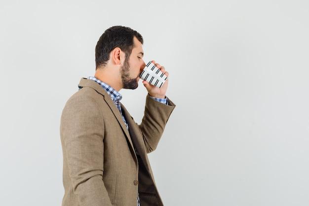 Jonge man in shirt, jasje koffie drinken en peinzend kijken.