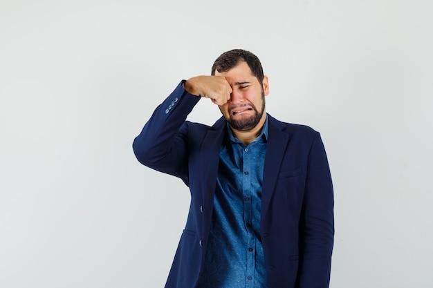 Jonge man in shirt, jasje oog wrijven terwijl huilen als een kind en beledigd op zoek, vooraanzicht.