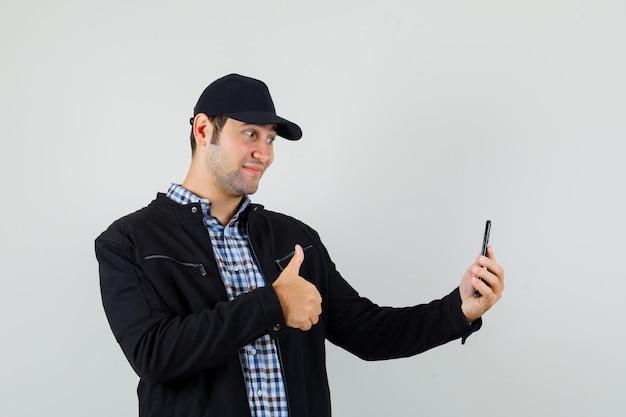 Jonge man in shirt, jasje, pet met duim omhoog terwijl hij selfie neemt en er blij uitziet