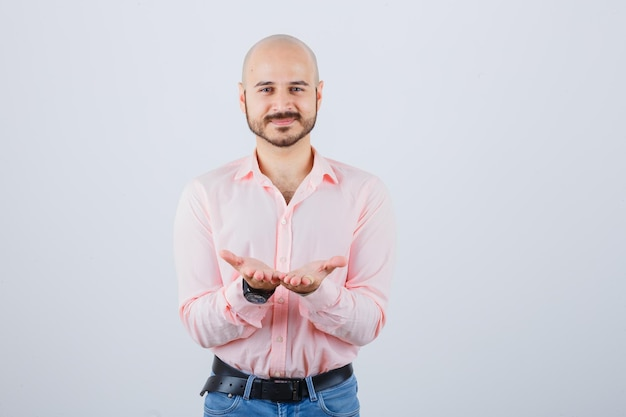 Jonge man in shirt, jeans die tot een kom gevormde handen uitrekt en er vredig uitziet, vooraanzicht.